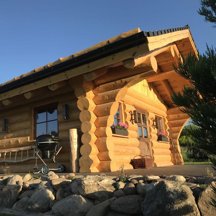 Gartenblockhaus Adler mit Grill bei strahlendblauem Himel